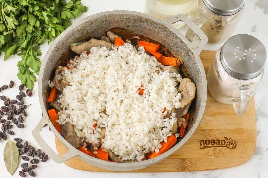 Когда все продукты обжарятся, всыпьте промытый рис.