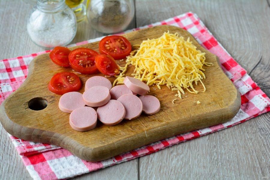Также для начинки нарежьте колечками сосиски, помидоры и натрите сыр на терке.