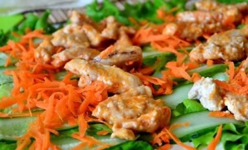 На морковь выкладываем кусочки курицы. Основную часть мяса выкладываем полоской, с таким расчётом, чтобы при заворачивании мясо оказалось в серединке. Остаток курицы распределяем на расстоянии 5-7 см от первой мясной полоски, тем самым получим ещё один мясной слой.