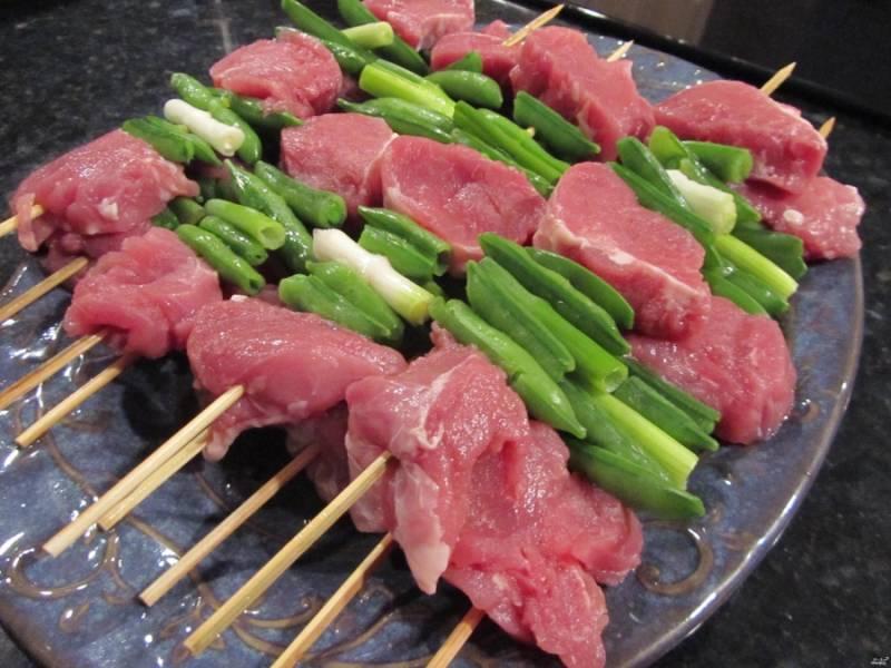 1. Все предельно просто - мясо нарезаем крупными кусками, промежуточно нанизываем молодой горошек и лук. Посыпаем солью и специями.