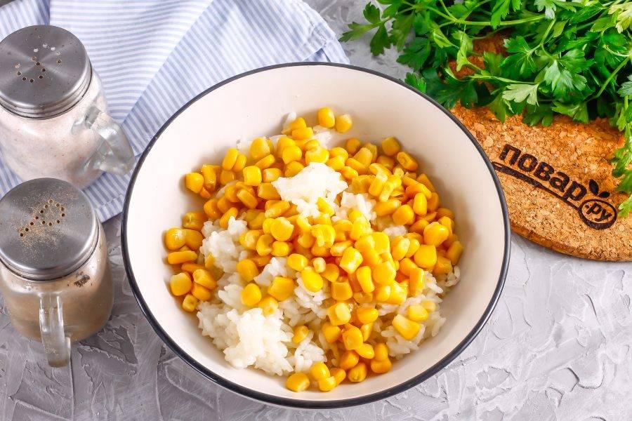 Остуженный отварной рис выложите в глубокую емкость. Вскройте банку с консервированной кукурузой и слейте маринад, выложите ее в емкость.