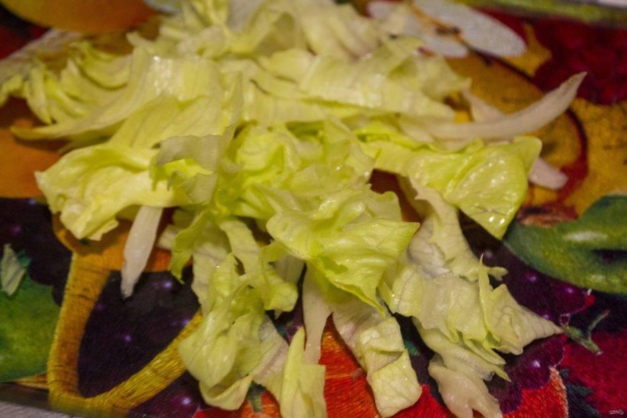 Салат очищаем от верхних листов и нарезаем поперек полосками 1 см шириной. При этом оставляем большой хороший лист для украшения.