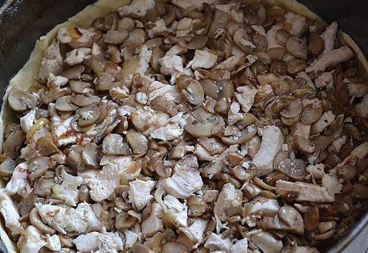 Теперь мы раскатываем тесто в круглый пласт и аккуратно переносим его в разъемную форму, смазанную сливочным маслом, из краев теста делаем небольшие бортики. Выкладываем на дно формы приготовленную начинку и равномерно ее распределяем.
