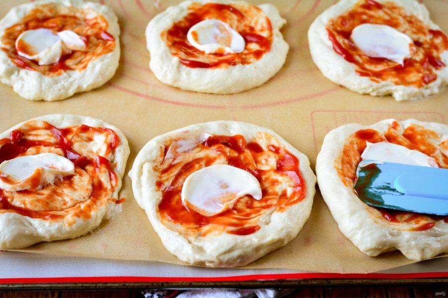 Разделите тесто на части и выложите мини-пиццу на противень. Руки смажьте растительным маслом, чтобы легче было работать с тестом. Тесту придайте форму пиццы. Смажьте соусом: кетчупом и майонезом.
