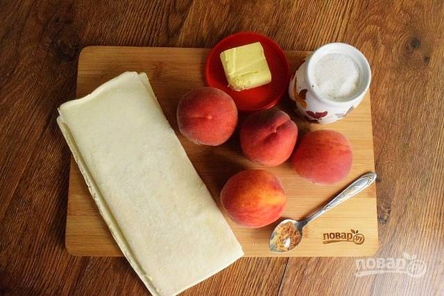Тесто заранее, за 20 минут достаньте из морозильника. Персики помойте, обсушите. Духовку включите и разогрейте до 180 градусов.