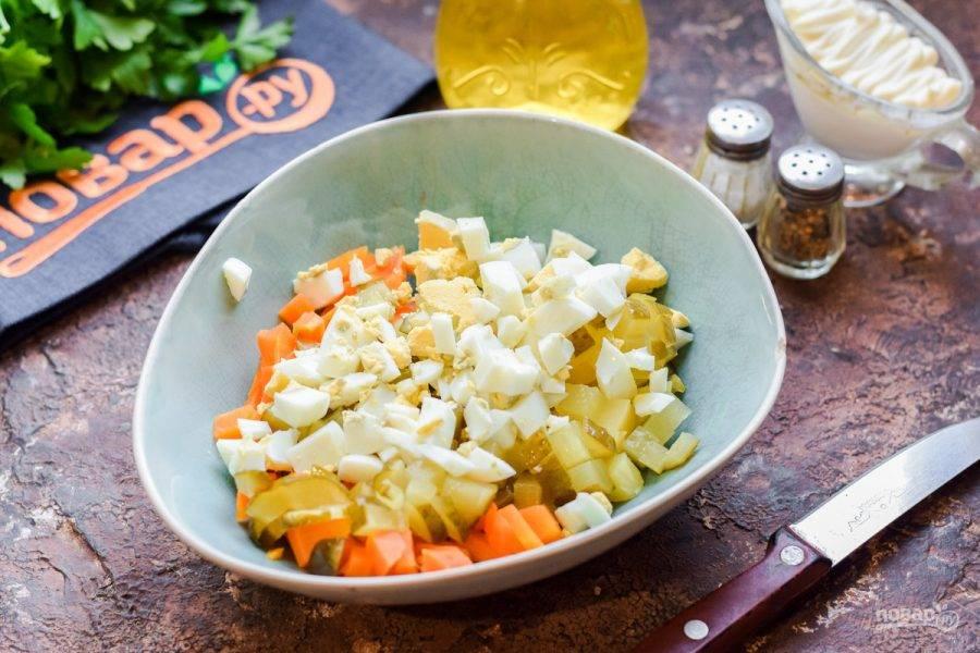 Куриные яйца нарежьте кубиками и добавьте в салат.