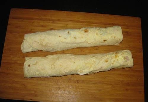 6. Плотно заверните рулет. Для удобства можно разрезать его пополам. Если время позволяет, заверните его в пищевую пленку и уберите в холодильник. После нарежьте порционными кусочками. Можно подавать к столу.