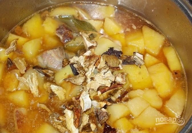 К картофелю с мясом добавьте специи, грибы, соль, перец и лавровый лист. Продолжайте томить блюдо на маленьком огне.