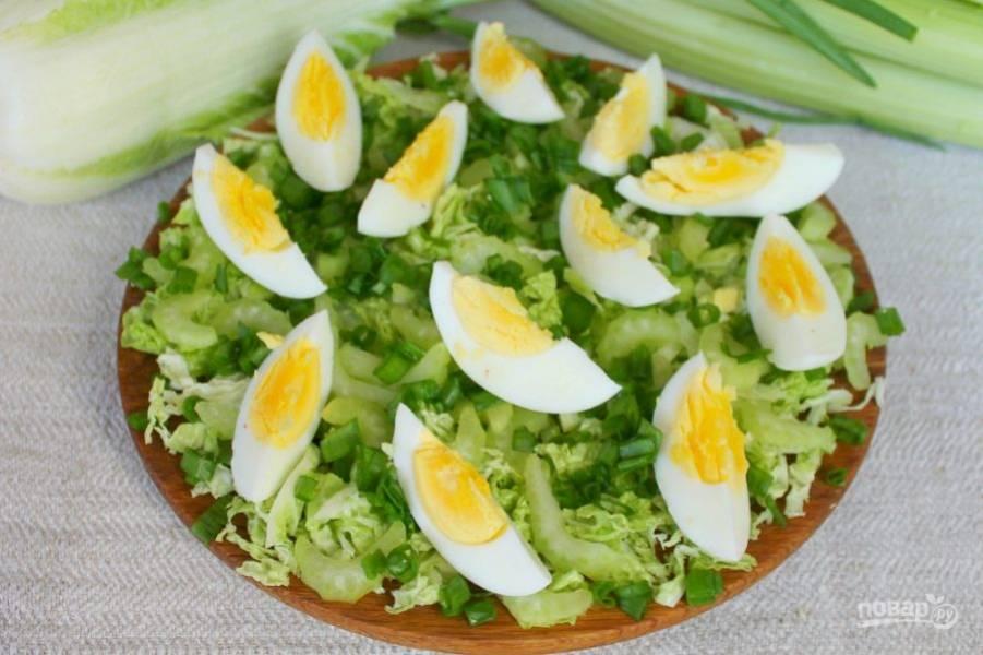 Вареные яйца чистим, режем на части и выкладываем сверху.