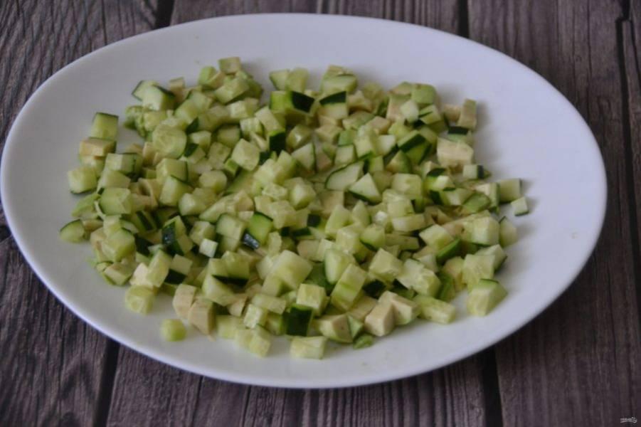 Кубиком нарежьте огурец и добавьте к авокадо.