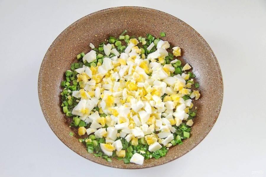 Готовьте его помешивая на небольшом огне около 5 минут. Добавьте нарезанные кубиками вареные яйца.