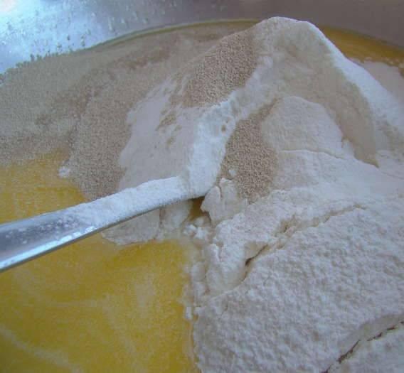 4. Массу нужно немного остудить и добавить соль с сахаром. Как следует перемешать, всыпать дрожжи и немного просеянной муки.