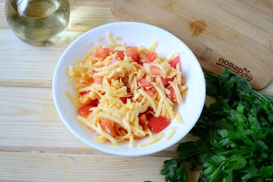 Пока подходит тесто, подготовьте начинку. Для этого мелко нарежьте помидор и натрите на крупной терке сыр. Смешайте помидоры с сыром.