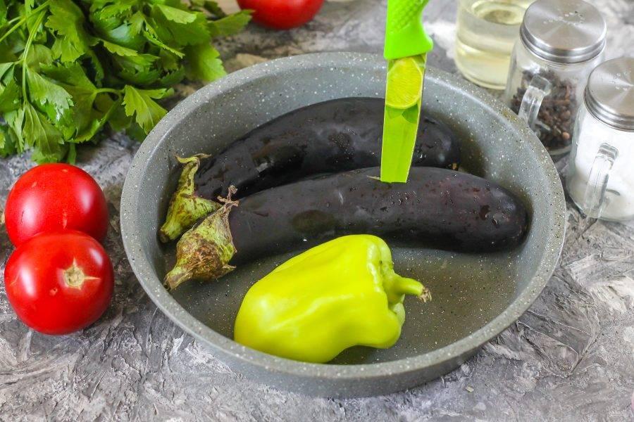 Баклажаны и болгарский перец промойте в воде, выложите в форму и наколите ножом в нескольких местах. Овощи обязательно нужно проколоть, чтобы они не лопнули при термической обработке. Разогрейте духовку до 200 градусов и поместите в нее форму.