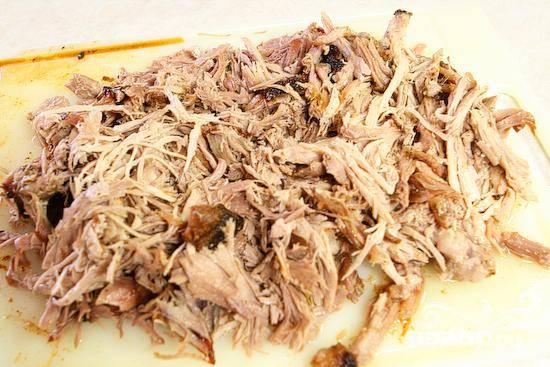 7. Выложить лопатку на большой разделочной доске и снять большую корку жира на поверхности. Измельчить мясо при помощи двух вилок и приправить специями по вкусу.