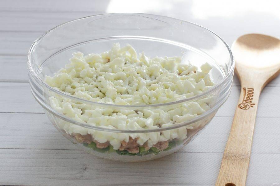 Яйца очистите и разделите на белки и желтки. На печень выложите натертый на крупной терке слой белков. Смажьте небольшим количеством майонеза.