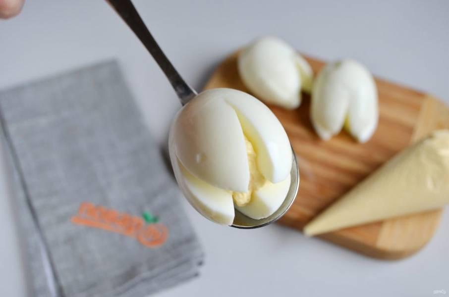 3. Желтки натрите на мелкой терке, добавьте тертый сыр, чеснок, соль, перец и ложку майонеза или сметаны. Перемешайте. Полученной массой наполните корнетик или кулинарный шприц. Фаршируйте белки яичной массой.