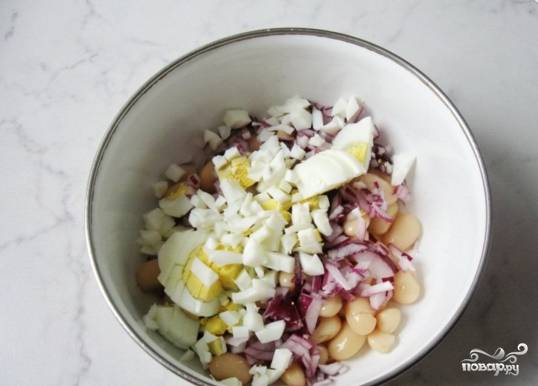 Отваренные вкрутую яйца охладите, почистите, нарежьте и добавьте к фасоли с луком.