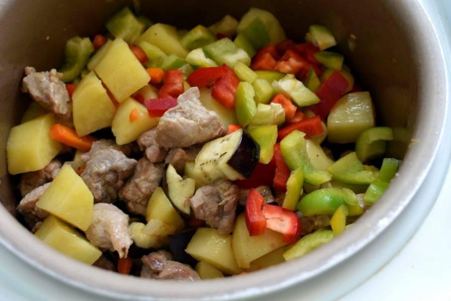 Выложите в мультиварку баклажаны и перец. Жарьте еще 3-4 минуты до румяности баклажанов.