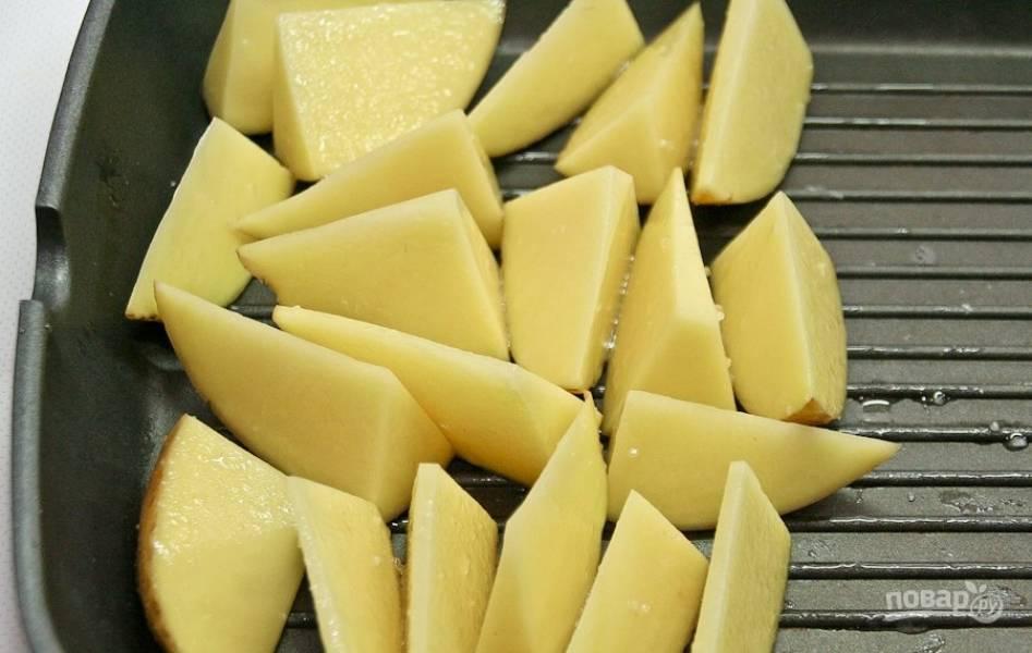 Промытый и нарезанный дольками картофель уложите на противень. Сбрызните его маслом и посолите. Отправьте картошку в разогретую до 220 градусов духовку на 5 минут.
