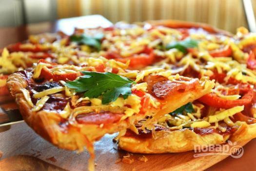 Готовую горячую пиццу посыпаем тертым сыром (а можно и за 10 минут до окончания готовки посыпать), разрезаем на части и подаем на стол.