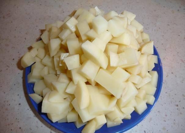 Через полчаса нарезаем картофель кубиками и отправляем его в кастрюлю к грибам, варим все еще минут 10.