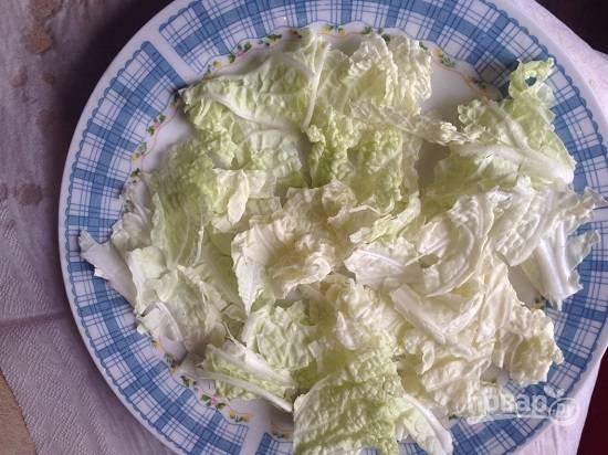 Листья салата или пекинской капусты рвем на кусочки и выкладываем на тарелку.