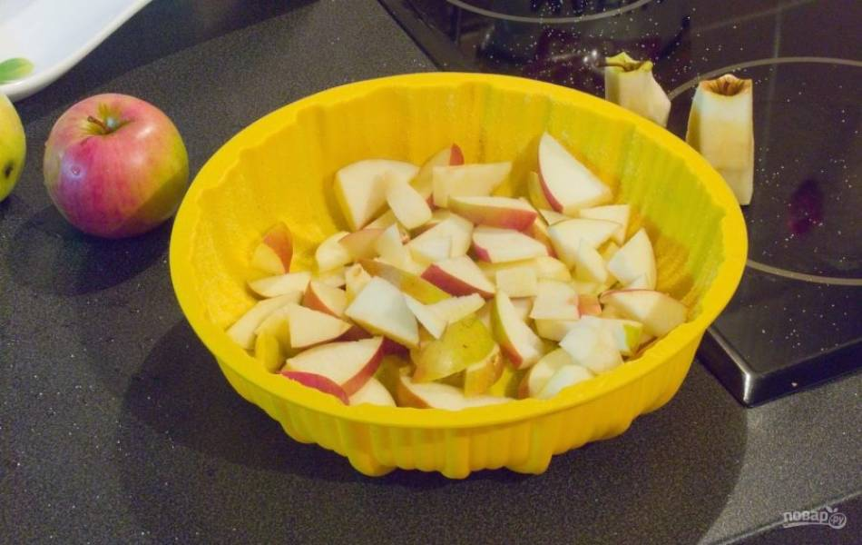 Яблоки промойте и нарежьте дольками. Уложите их на дно.