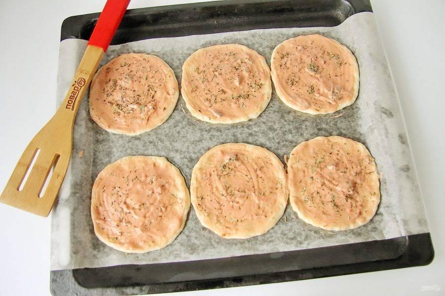 Смажьте тесто соусом и посыпьте ароматными травами.