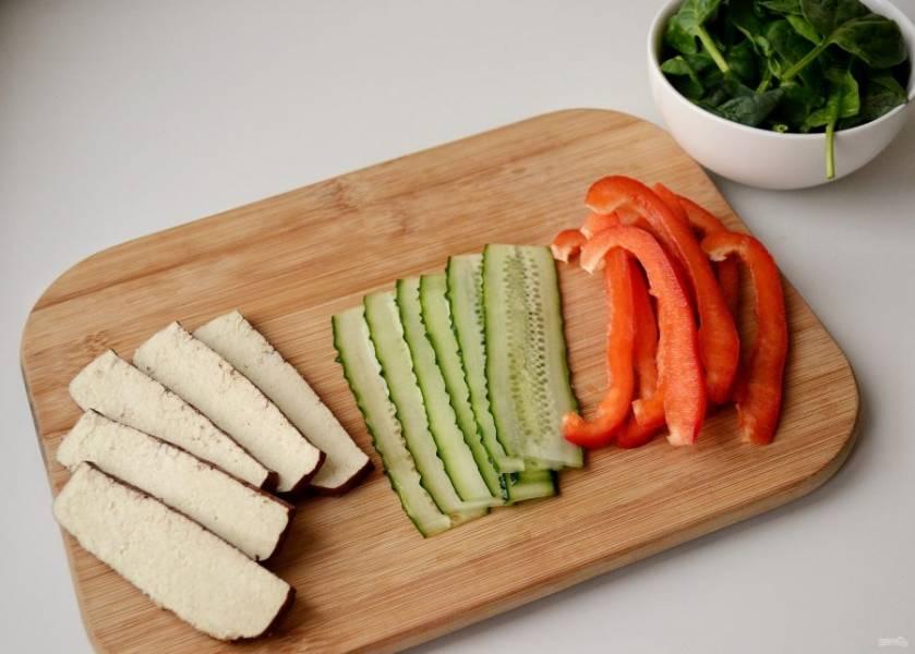 Промойте и высушите свежий шпинат. Тофу нарежьте пластинками по полсантиметра. Разрежьте огурцы вдоль на тонкие ломтики. Перец разрежьте пополам, после нарежьте каждую половину на тонкие полосочки.