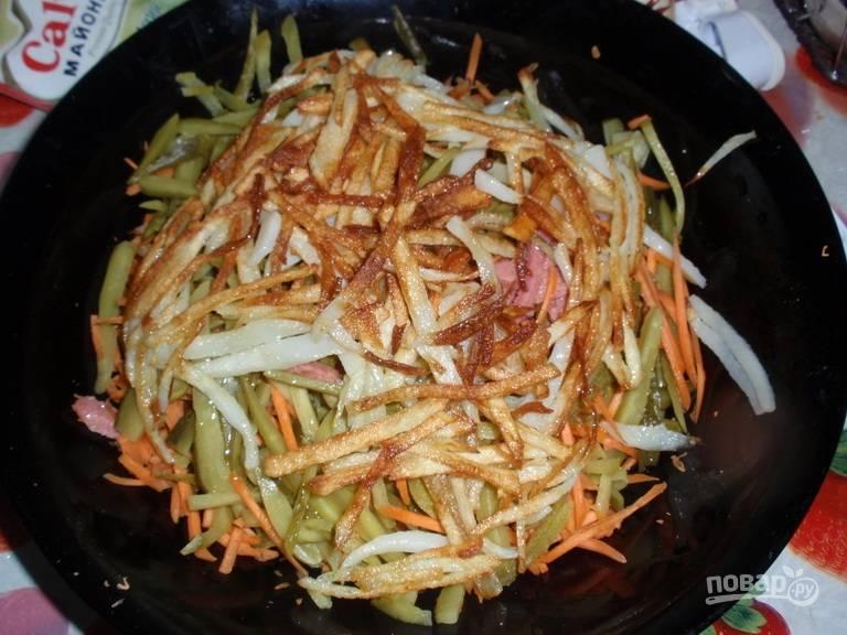 Удалите лишнее масло, добавьте остывший картофель к остальному салату.