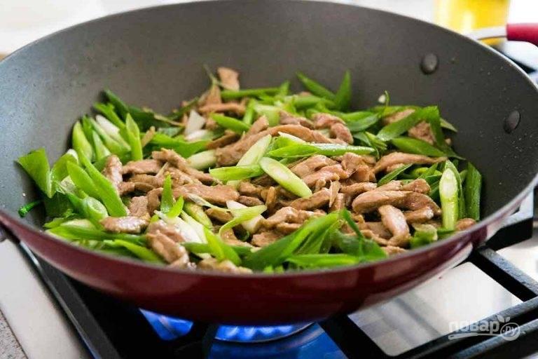 4.Нарежьте перьями зеленый лук. Выложите к мясу, обжаривайте еще 1-2 минуты и снимите сковороду с огня.