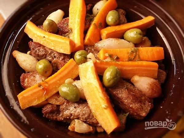 Морковь очистите и вымойте под проточной водой. Нарежьте ее крупными брусочками и выложите на мясо в виде звезды. Сверху положите несколько крупных зеленых оливок.