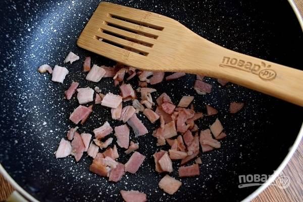 Сухую сковороду нагрейте. Бекон измельчите и обжарьте до румяной корочки.