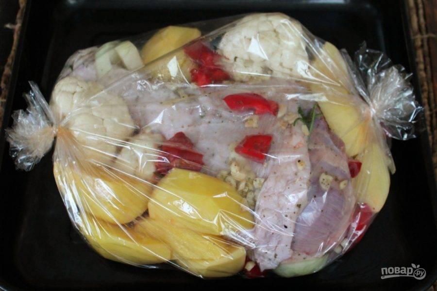 Овощи отправляем в рукав для запекания, выкладывая вокруг индюшатины. Ставим в холодную духовку. Включаем на 180-190 градусов. Запекаем полтора часа после того, как рукав вздуется.