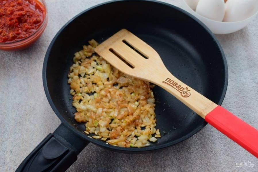 Лук, чеснок очистите и измельчите. В глубокой сковороде разогрейте растительное масло, пассеруйте измельченные лук и чеснок до мягкости, добавьте молотые кориандр, зиру и паприку.