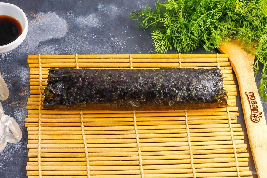 Аккуратно сверните нори с начинкой, используя коврик. Незаполненную часть нори смажьте водой и докрутите ролл до конца.