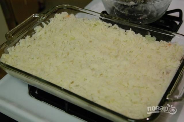 14.Смешайте картофель с тертым пармезаном, выложите поверх мясного слоя картофельное пюре, распределите его по всей форме.