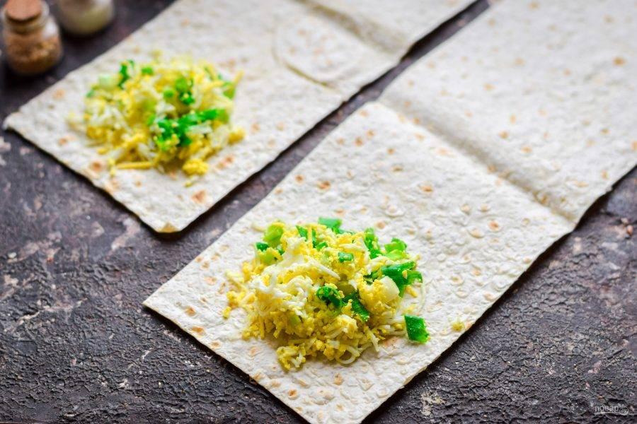 Лаваш нарежьте полосками. На край полоски выложите начинку из яйца и лука.