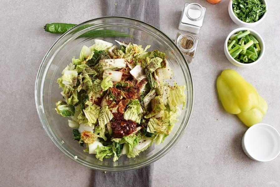 Добавьте красный перец, перечную пасту, немного посолите и поперчите по вкусу. Влейте уксус и соевый соус. Хорошо перемешайте, немного перетирая, чтобы капуста окрасилась в цвет перца.