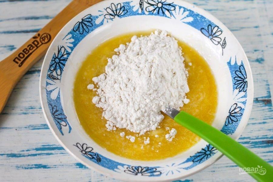 Всыпьте просеянную пшеничную муку вместе с разрыхлителем, замесите плотное песочное тесто.