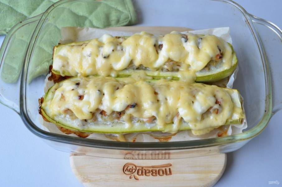 Готовые лодочки из кабачков полейте соусом (майонез+сметана) и посыпьте тертым сыром. Оставьте в духовке еще на 5-7 минут. Готово! Подавайте закуску горячей!
