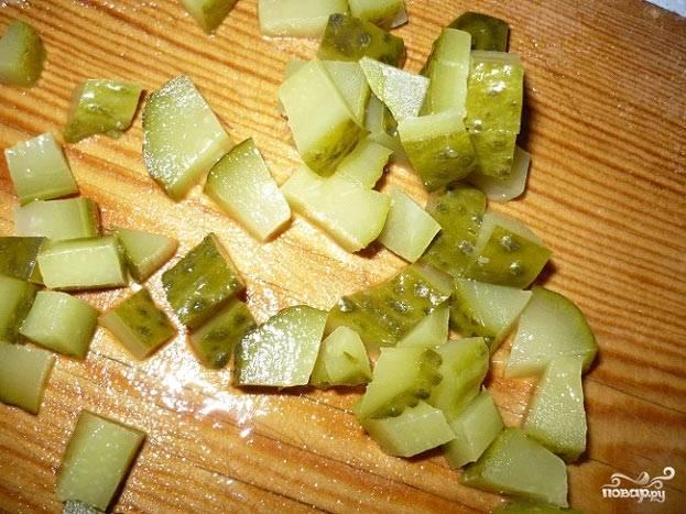 Соленый огурец нарезаем кубиками с помощью острого ножа. Огурчик придаст пикантность и свежесть нашему блюду.