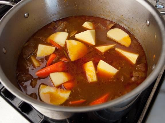 7. За это время можно подготовить картофель и морковь. Их необходимо вымыть, очистить и нарезать. Добавить к мясу и готовить еще около 30 минут, пока овощи не станут мягкими.