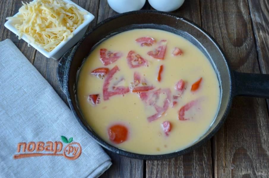 Смажьте сковороду сливочным маслом, обжарьте помидоры буквально одну минутку, огонь сильный. Влейте омлет, сверху посыпьте зеленью, распределите тертый сыр. Уменьшите огонь до минимума и томите омлет под крышкой до готовности.
