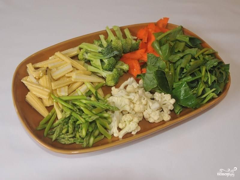 Обжаренную лапшу отставьте в сторону, а пока приготовьте овощи и соус. Овощи порежьте: морковку кружочками, мини-кукурузу и спаржу — соломкой, капусту кале порежьте широко на полоски (по типу лапши), а брокколи и цветную капусту разделите на соцветия.