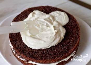 4.Остывшие бисквитные коржи выньте из форм. Перемажьте сметанным кремом, укладывая друг на друга. Верх и бока торта также обильно смажьте кремом.