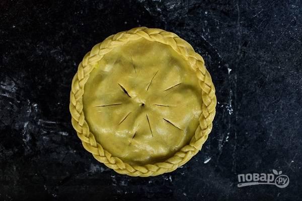6. Сделайте надрезы для выхода пара. Остатками теста можно украсить пирог вот такой косичкой, например. Отправьте пирог в разогретую до 200 градусов духовку, смазав предварительно желтком.