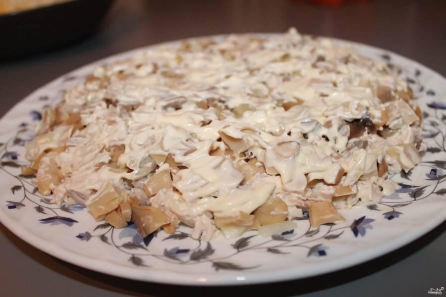 Консервированные шампиньоны мелко нарезаем и соединяем с измельченным луком. Выкладываем поверх куриного мяса. Смазываем майонезом.
