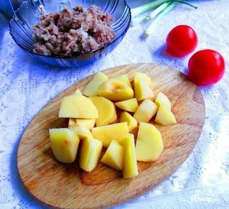 3. А тем временем очистите картофель, нарежьте его небольшими кубиками. Откройте тушенку, разомните крупные кусочки при необходимости.